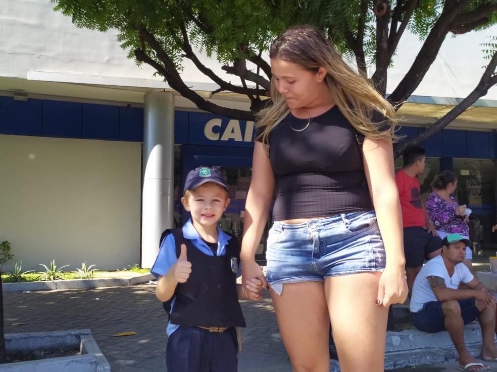 Vendedora Ana Carolina Souza com o filho Lorenzo, que se caracterizou com roupas da polícia para acompanhar o desfile — Foto: Halisson Ferreira/SVM