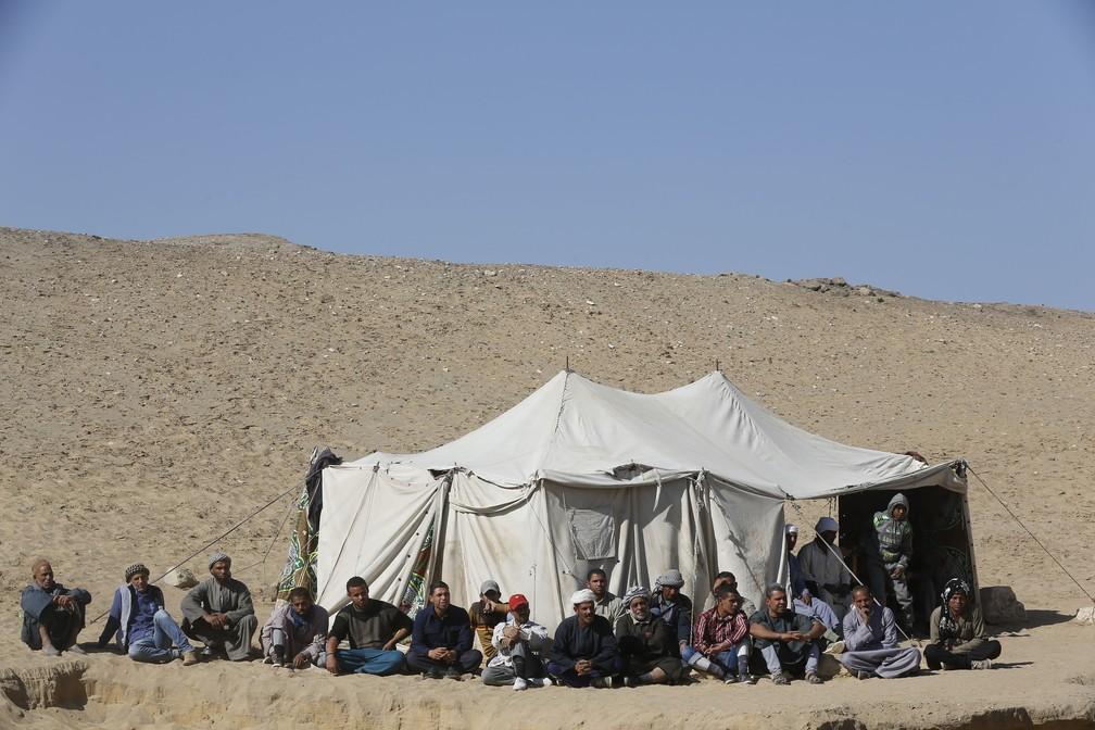 Escavadores ouvem a conferência de imprensa do Ministro de Antiguidades no local da pirâmide de degraus de Saqqara, em Gizé (ou Giza). — Foto: AP Photo / Amr Nabil