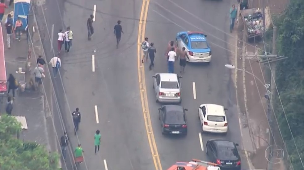 Homem chuta viatura da PM na Rua Edgard Werneck durante manifestação de moradores da Cidade de Deus — Foto: Reprodução/TV Globo