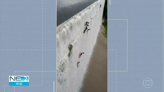 Homens entram em barragem e tomam banho pendurados em paredão de 16 metros de altura; veja vídeo