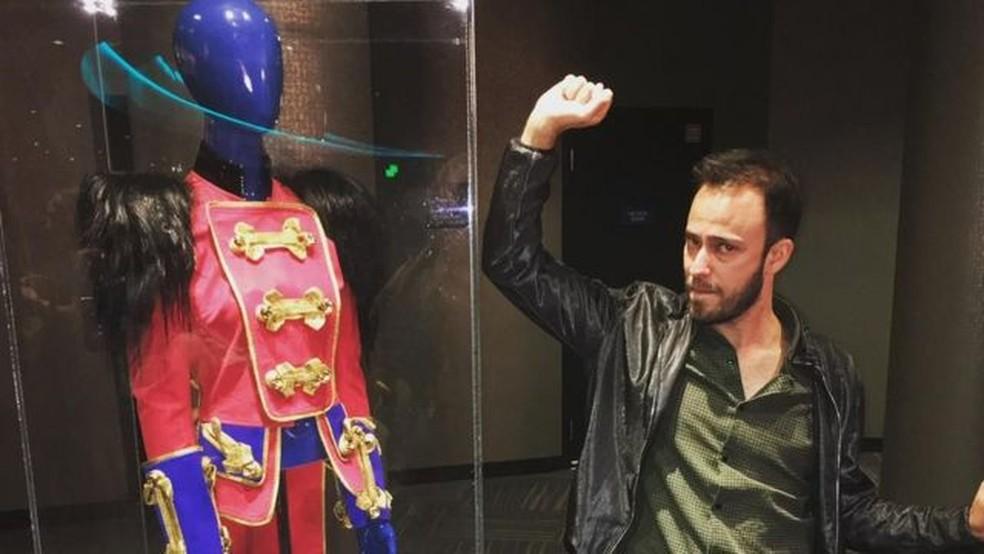 Alan Mangabeira, fã de Britney desde os 11 anos e autor de doutorado sobre seu fandom, com os figurinos da cantora na exposição do show Piece of Me, em Las Vegas — Foto: ALAN MANGABEIRA/ARQUIVO PESSOAL via BBC
