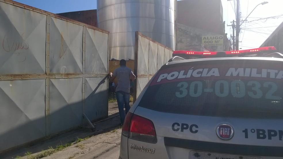 Portão por onde os suspeitos entraram fica no fundo do supermercado, e era fechado com um fio (Foto: Matheus Tenório/G1)