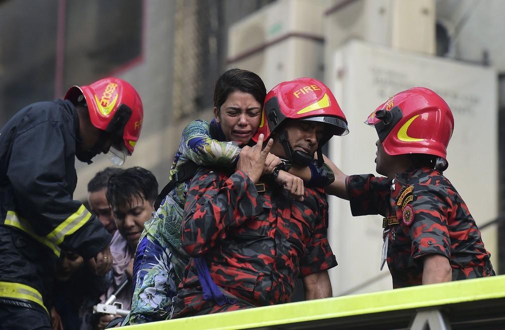 Sobrevivente de incêndio em prédio comercial de Daca, em Bangladesh, é socorrida pelos bombeiros  — Foto: Munir Uz Zaman / AFP