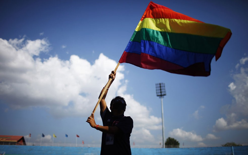 Membro da comunidade LGBT de Catmandu ergue uma bandeira do orgulho gay na cerimônia de abertura da 1ª edição dos Jogos LGBT do Sul da Ásia, na capital do Nepal. — Foto: Niranjan Shrestha/AP