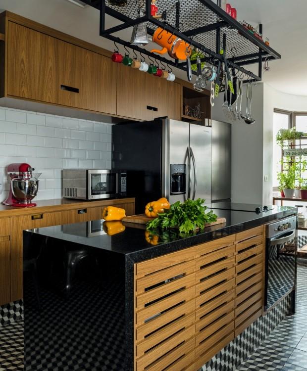 A estante suspensa tem estrutura de ferro e tela metálica perfurada, materiais que dão um ar industrial à cozinha (Foto: Edu Castello / Editora Globo)