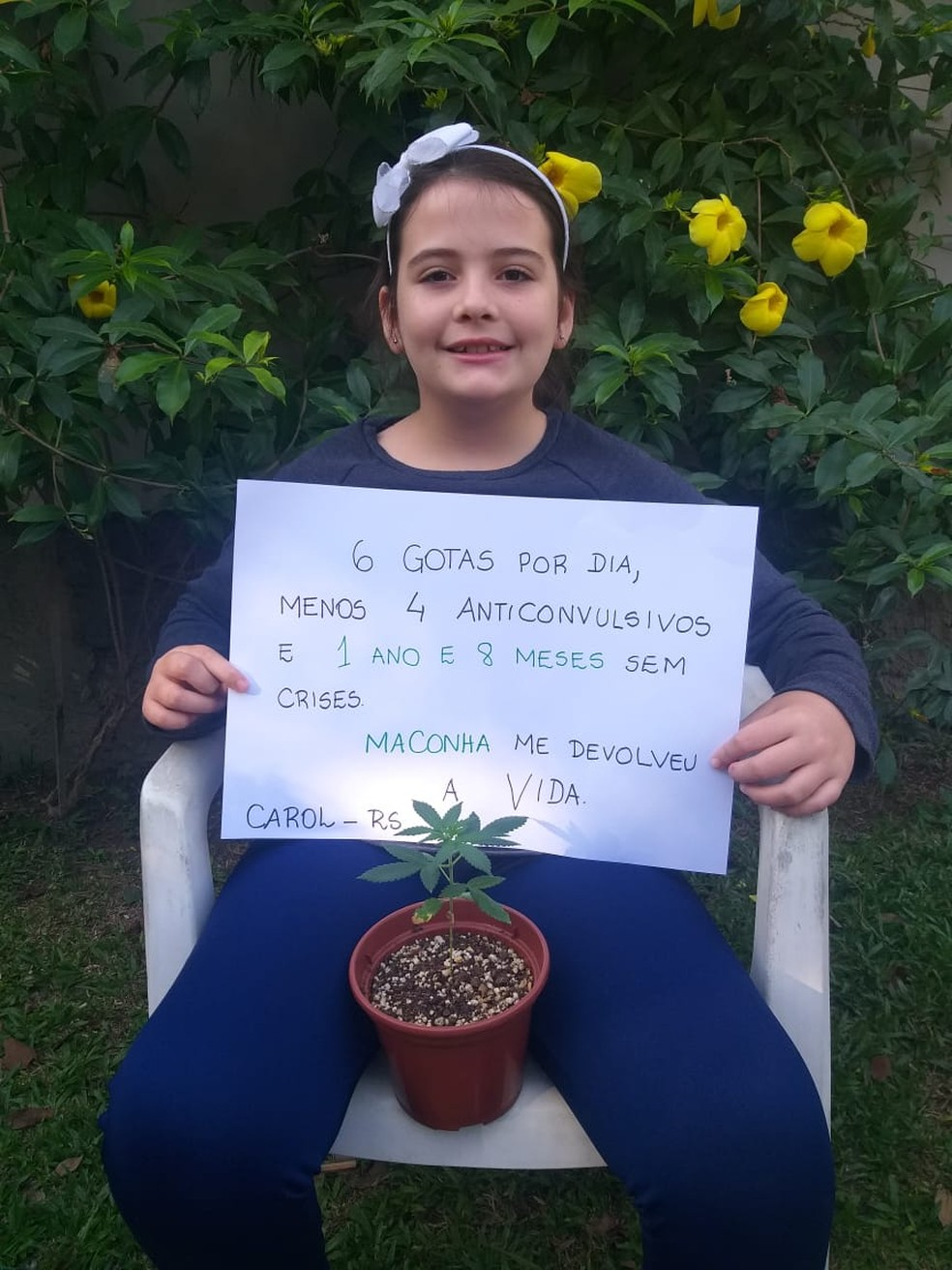 Caroline Pereira da Silva, de 10 anos, com uma muda de maconha e um cartaz onde explica como o uso diário do óleo artesanal mudou a sua vida. — Foto: Arquivo pessoal