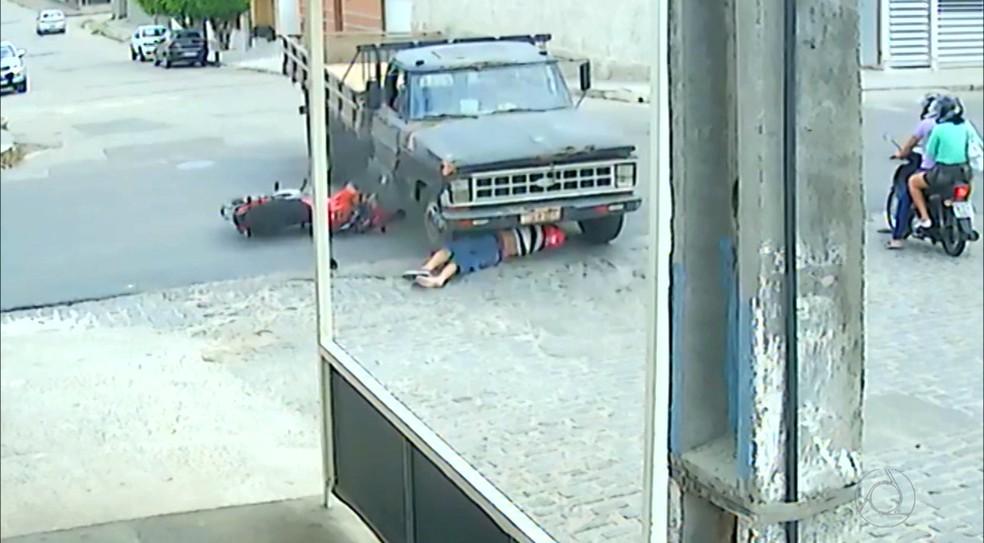Motociclista foi parar embaixo do caminhão, mas escapou apenas com arranhões (Foto: Reprodução/TV Cabo Branco)