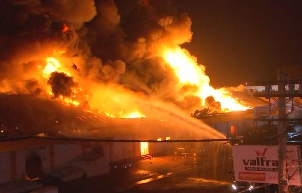 Bombeiros jogam água para tentar controlar as chamas no telhado da loja (Foto: Reprodução/TV TEM)