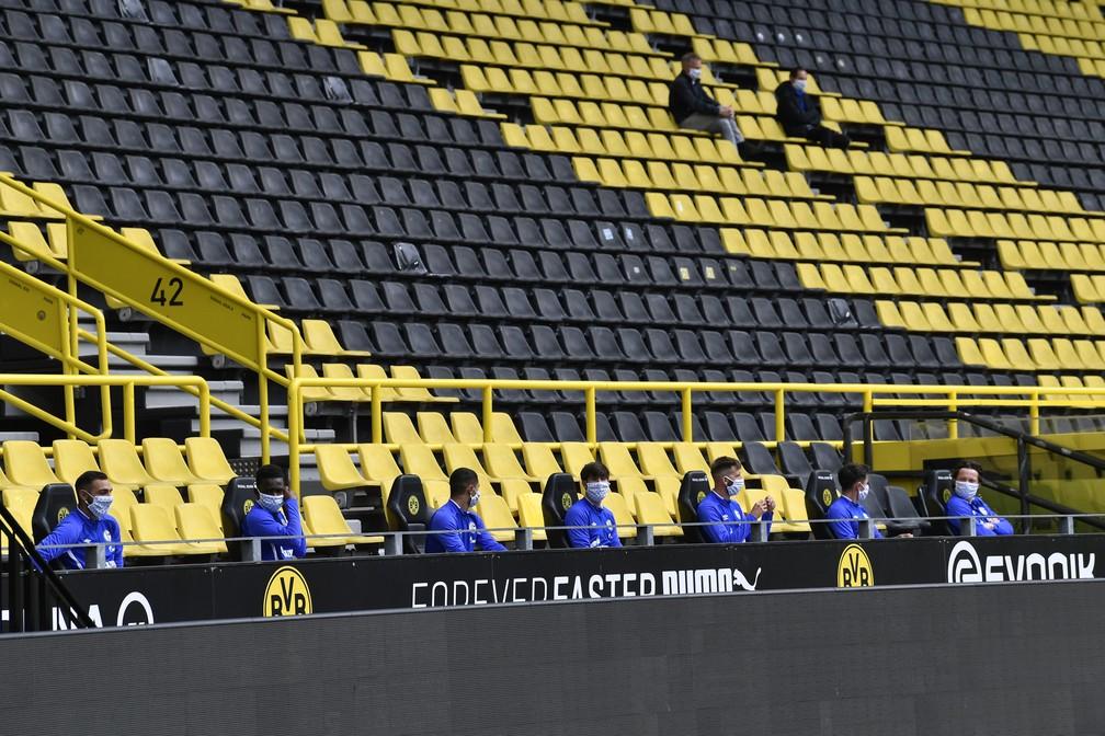 Jogadores reservas do Schalke de máscaras e sentados em bancos mais distantes — Foto: Martin Meissner/Getty Images