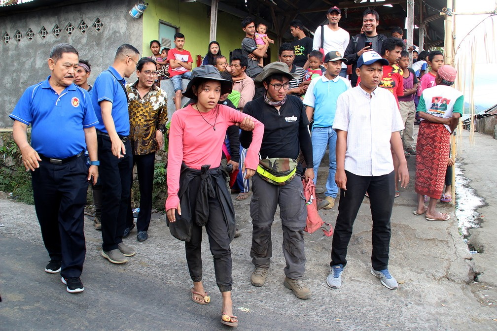 Montanhistas que desceram do monte Rinjani (ao centro, de rosa e de preto) chegam nesta segunda-feira (30) em um posto em Sembalun, na Indonésia (Foto: Pikong/AFP)