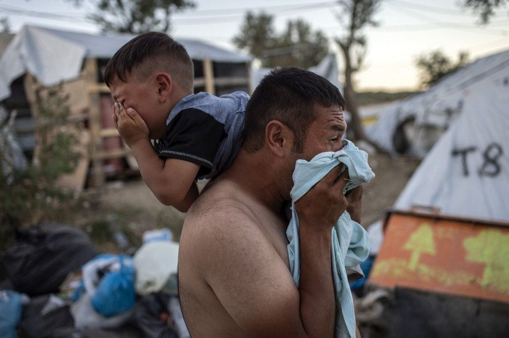Father and son cry after fire in migrant camp on Lesbos island in Greece on Sunday (29) - Photo: Angelos Tzortzinis / AFP