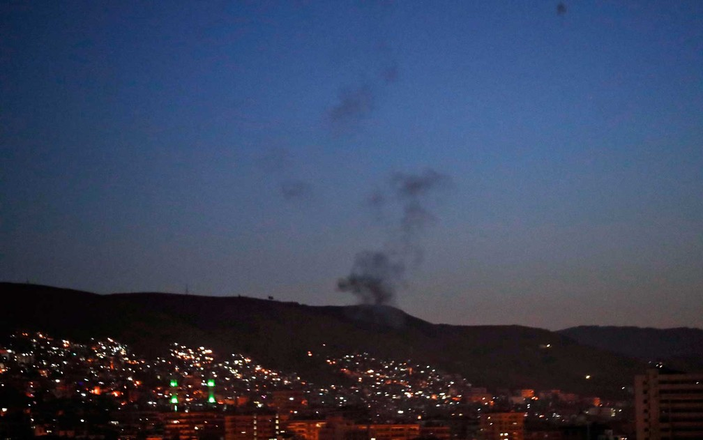 Foto mostra fumaça após ataques aéreos contra diferentes partes da capital síria (Foto: Hassan Ammar / AP Photo)