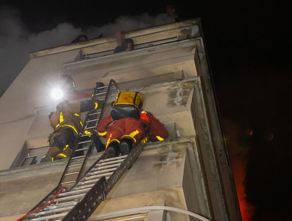 Bombeiros socorrem moradores atingido por incêndio em prédio em Paris — Foto: Benoît Moser / Brigada dos Sapeurs-Pompiers de Paris / via Reuters