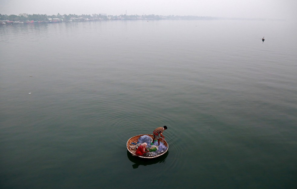 Um pescador e sua esposa pegam peixes nas águas do lago Vembanad em Kochi, na Índia (Foto: Sivaram V/Reuters)