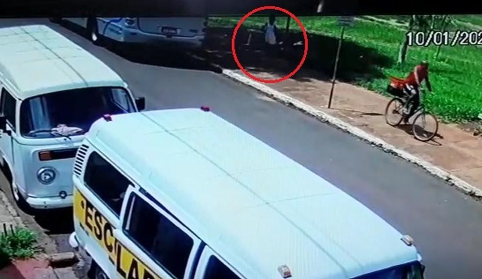 Suspeito aparece de camiseta vermelha em uma bicicleta — Foto: Divulgação/Câmeras de Segurança
