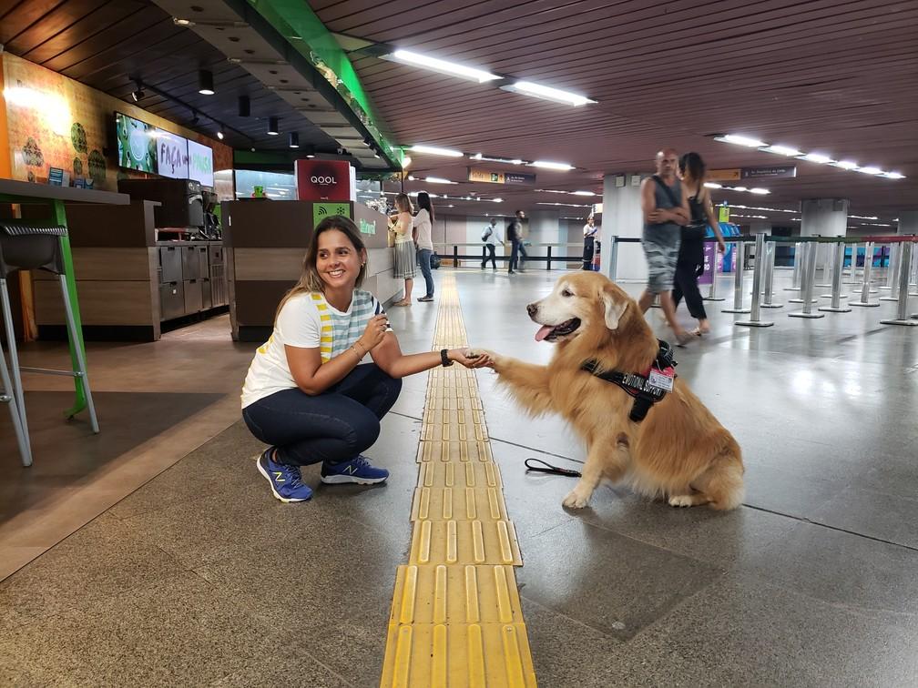 Danielle Christo e seu golden retriever Prince of Persia na Estação Carioca do metrô — Foto: Eduardo Pierre/G1