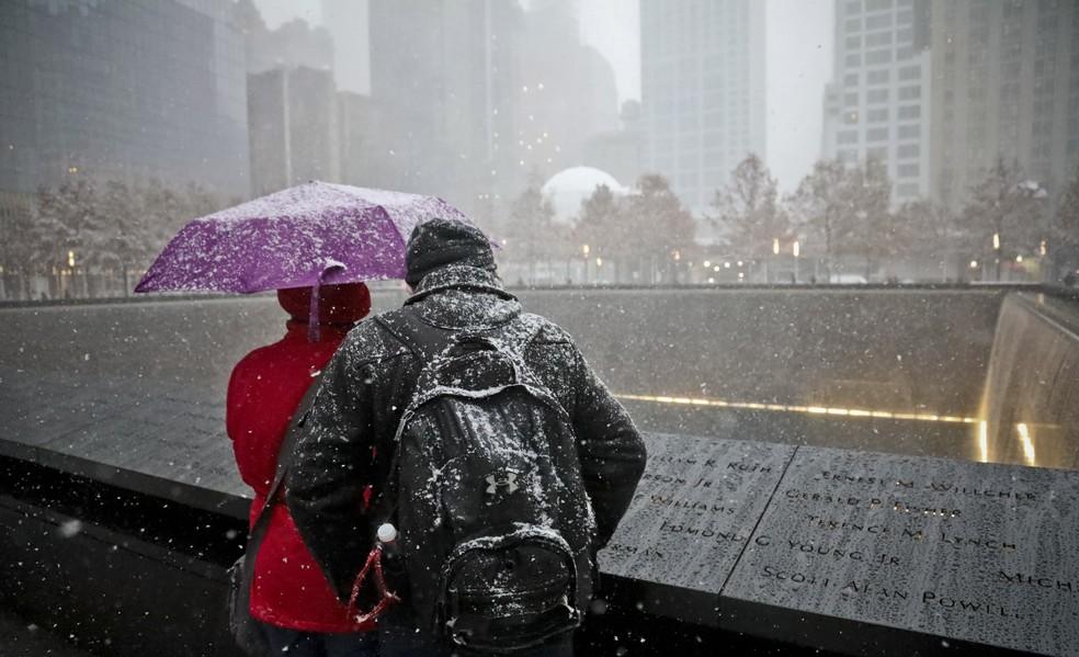 Visitantes no Memorial de 11 de Setembro observam obra sob neve e chuva, em Nova York, na quinta-feira (15) — Foto: Bebeto Matthews/AP Photo