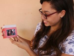 Aline mostra uma caixa de fotos que tem dela e do namorado (Foto: Maria Caroline Palieraqui/G1 MS)