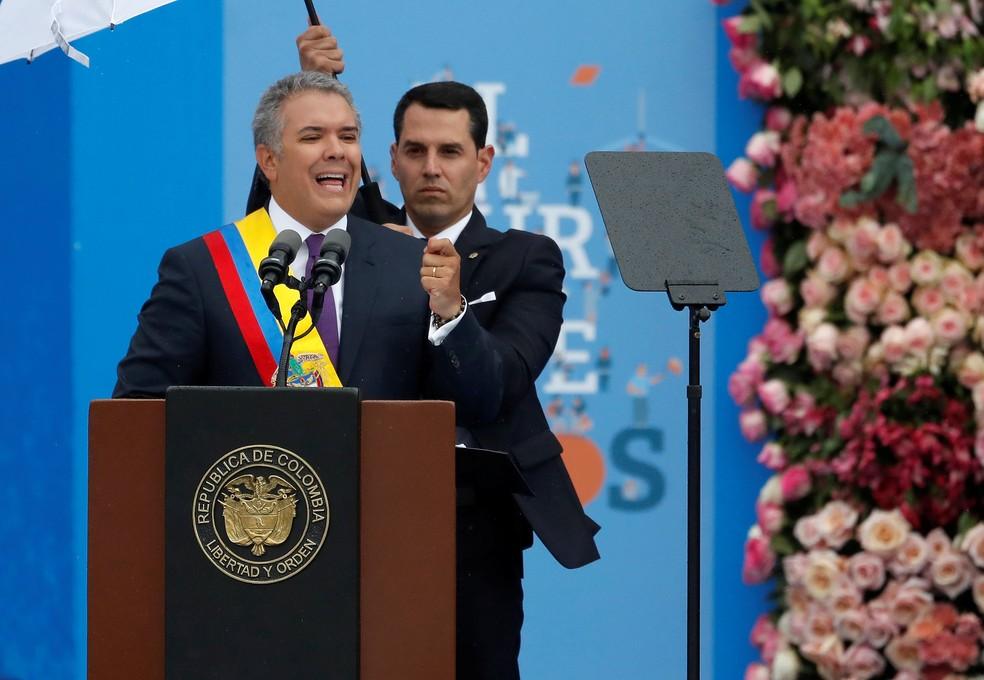 -  O novo presidente da Colômbia, Iván Duque, discursa debaixo de guarda-chuva em cerimônia de posse em Bogotá  Foto: Reuters/Carlos Garcia Rawlins