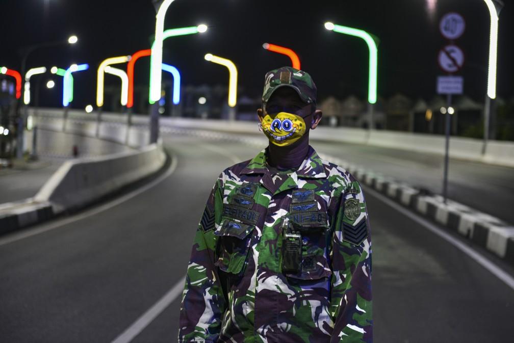 Um soldado usando máscara facial com o personagem de desenho animado Bob Esponja, vigia uma estrada deserta em Banda Achém, na Indonésia  — Foto: Chaideer Mahyuddin/AFP