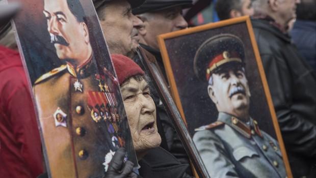 Comunistas carregam retratos do ex-líder soviético Josef Stalin durante marcha em Moscou (Foto: Denis Tyrin/AP)