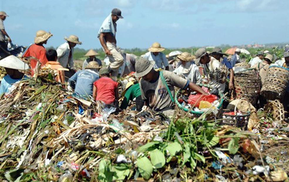 Grupo de catadores procuram plásticos e garrafas para reciclagem em Bali, na Indonésia (Foto: AFP)