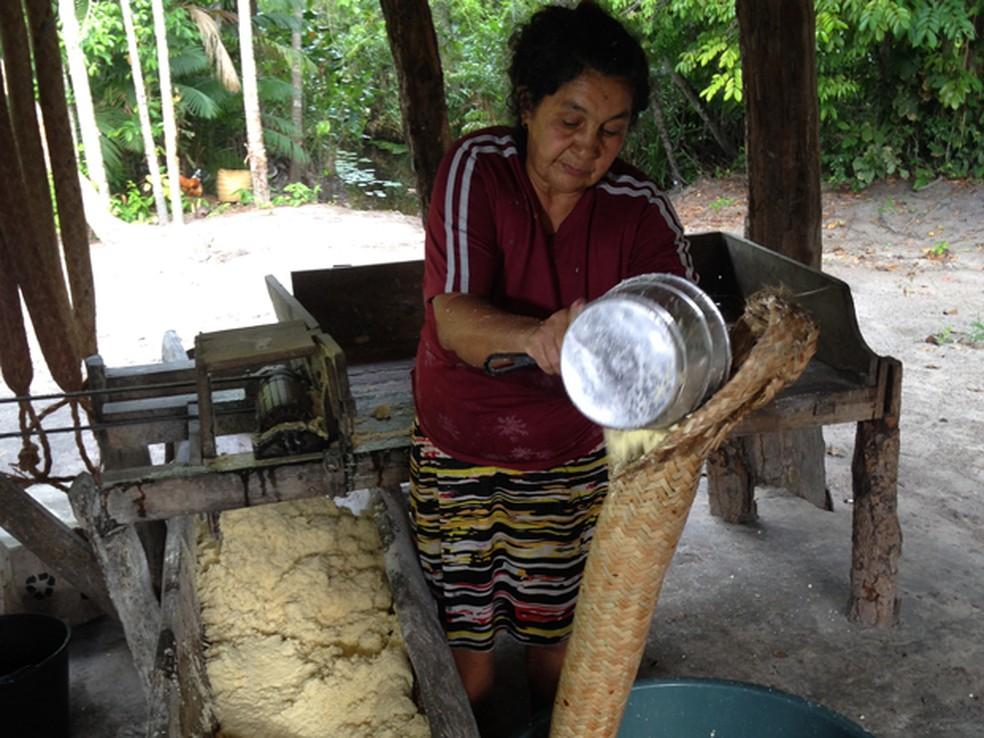 Produtora Nazaré armazenando mandioca moída em tipiti — Foto: Clarissa Carramilo/G1