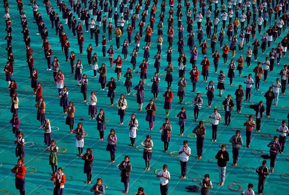 Crianças participam de sessão de ioga no último dia de um acampamento, em Ahmedabad, na Índia (Foto: Amit Dave/Reuters)