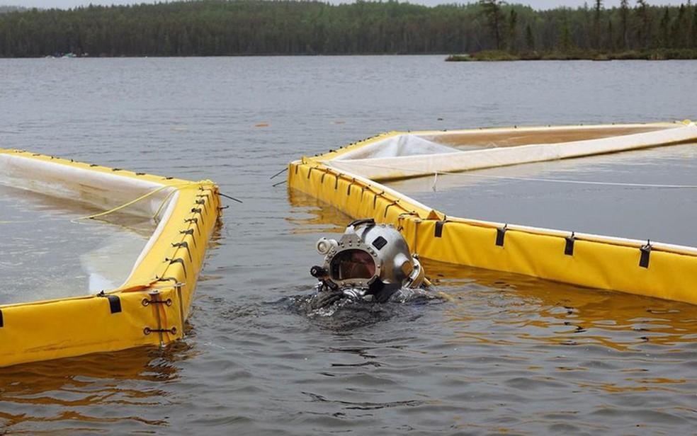 Mergulhador coloca sacos de areia debaixo d'água para proteger o local onde será realizado o experimento (Foto: BBC/Lesley Evans Ogden)
