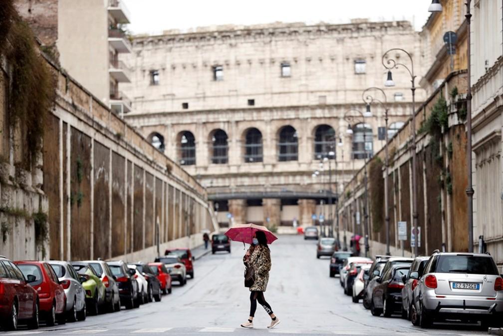 Pedestre com máscara na frente do Coliseo, em Roma, na Itália — Foto: Yara Nardi/Reuters