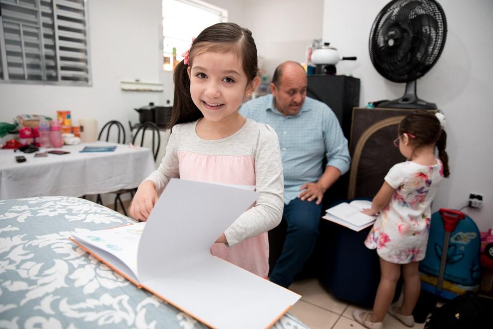 Valentina e sua irmã mais nova, Rafaela (ao fundo), folheam exemplares do livro escrito por ela na casa da família, no Brás, sob o olhar do pai, Cristiano (Foto: Marcelo Brandt/G1)