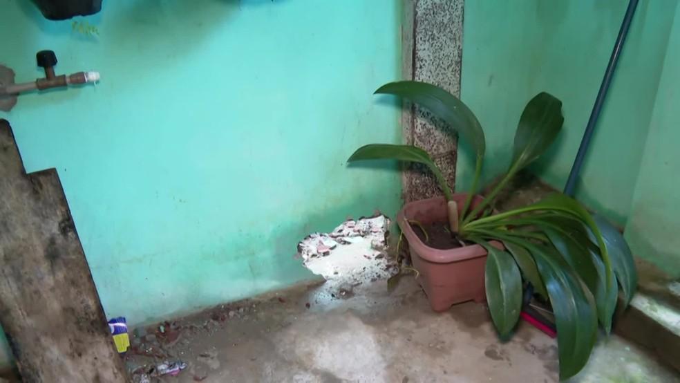 Moradora na Rua Irmãs Fox, em São Lourenço da Mata, contou que precisou abrir um buraco na parede para escoar a água — Foto: Reprodução/TV Globo