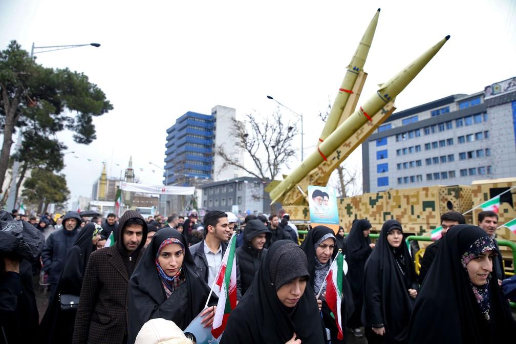 Iranianos passam por um míssil durante uma manifestação que marcou o 40º aniversário da Revolução Islâmica de 1979, em Teerã, nesta segunda-feira (11)  — Foto: Ebrahim Noroozi/AP