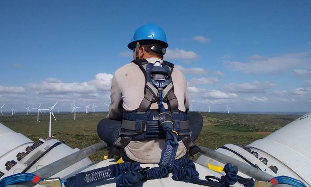 Leonardo Morais, de costas, sobre uma torre de energia eólica. Ele foi aluno da primeira turma de um curso superior voltado para o setor no Brasil   — Foto: Arquivo pessoal/cedida