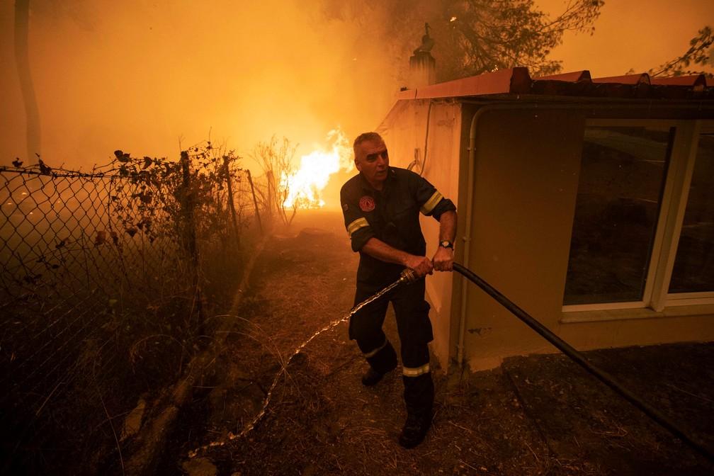 Um bombeiro puxa uma mangueira, enquanto um incêndio ocorre na aldeia de Pefki, na ilha de Evia, na Grécia, em 8 de agosto de 2021. — Foto: REUTERS/Nikolas Economou