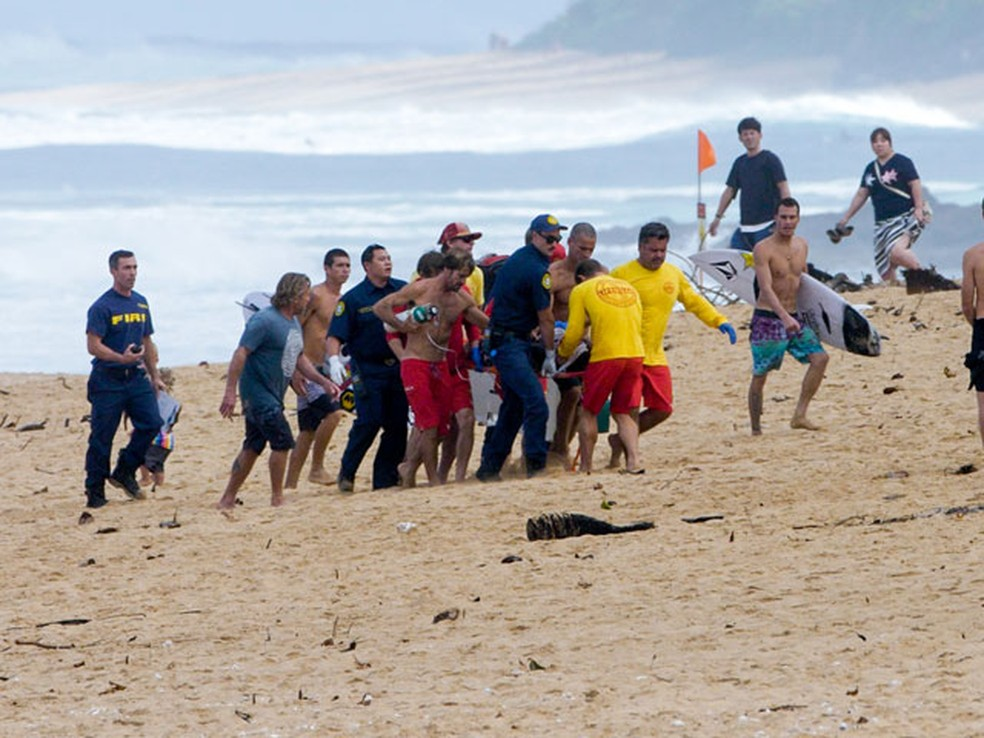 Guilherme Tâmega (short vermelho, sem camisa) e outros sal-vidas fazem o resgate a Dusty Payne após grave acidente  (Foto: Tyler Rock/FreeSurf)