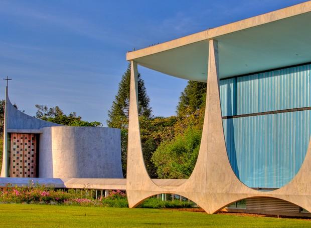 As pilastras tão características do desenho de Niemeyer se transformaram na identidade do Distrito Federal. Ao lado, a capela dedicada à Nossa Senhora da Conceição tem vitrais de Athos Bulcão (Foto: Ichiro Guerra/Reprodução)