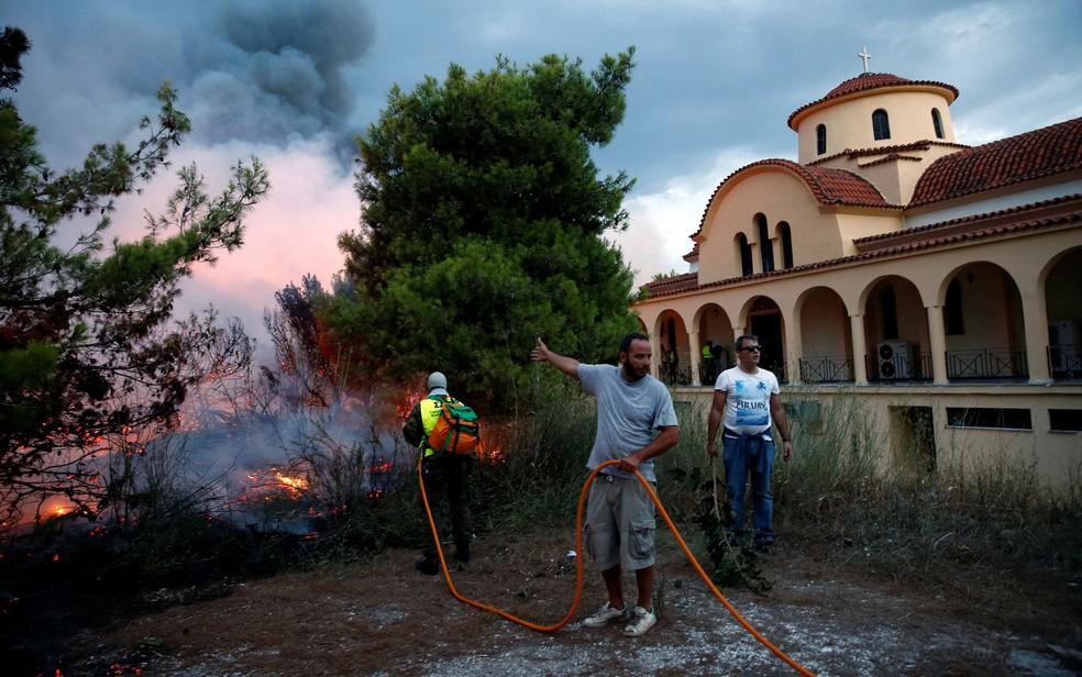 Moradores tentam extinguir chamas de incêndio florestal que ameaçam igreja na cidade de Rafina, perto de Atenas, na Grécia, na segunda-feira (23) (Foto: Reuters/Costas Baltas)