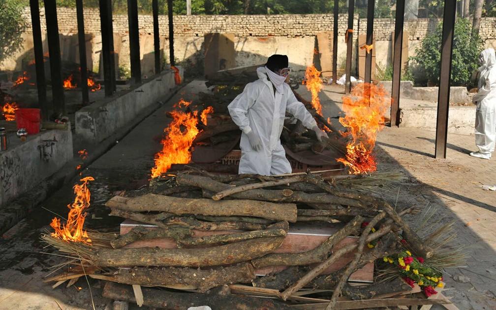 Homem prepara fogo para queimar mais uma vítima da Covid na Índia — Foto: Channi Anand / AP Photo
