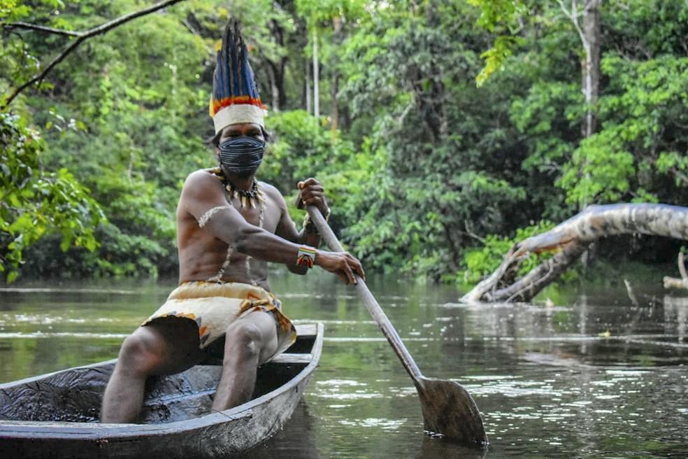 Indígena Huitoto navega em rio na região de fronteira do Amazonas com a Colômbia — Foto: Tatiana de Nevó / AFP