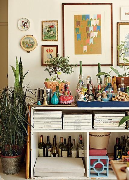 O nicho de um antigo guarda-roupa agora acomoda o bar e revistas, na casa do diretor de arte de cinema Thiago Bastos. A decoração mistura garrafas cheias e vazias a plantas, obras de arte e pratos na parede (Foto: Victor Affaro/Casa e Jardim)