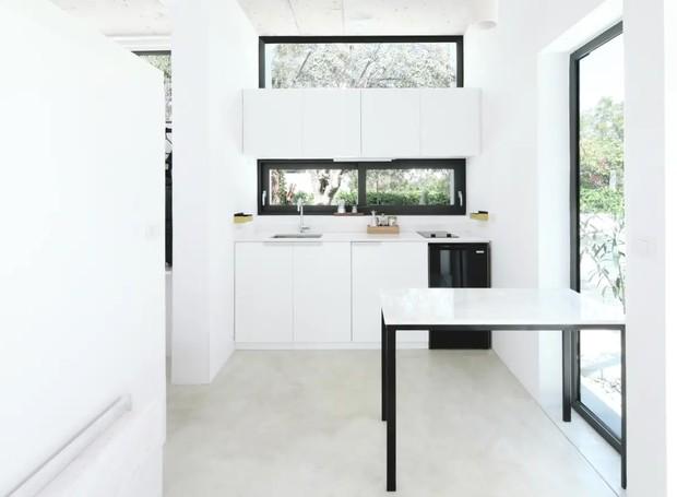 A cozinha branca é prática e pequena. Os gabinetes foram feitos sob medida para garantir funcionalidade (Foto: Apartment Therapy/ Reprodução)