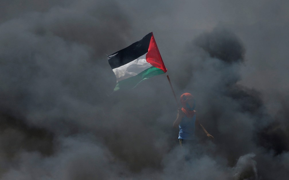 Garoto é visto com uma bandeira da Palestina durante confronto após protesto contra a inauguração da embiaxada dos EUA em Jerusalém (Foto: Mohammed Salem/Reuters)