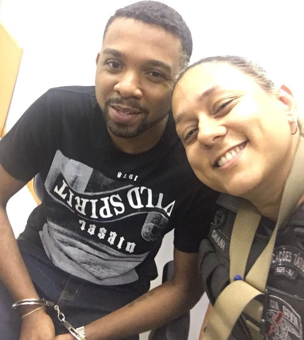 Algemado e sorridente, Rogério 157 posa para selfie com policial (Foto: Redes sociais)