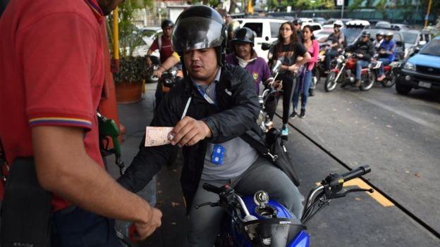 Motorista paga 50 bolívares pelo combustível, o equivalente a menos de um centavo de dólar (Foto: Getty Images via BBC News Brasil)