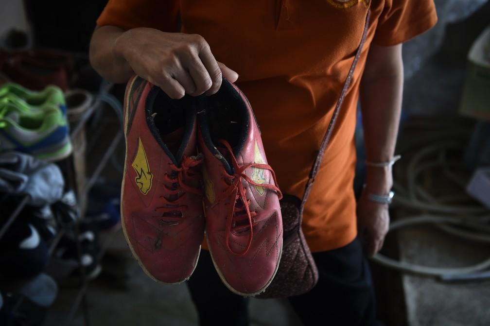 Tia-avó de garoto preso em caverna na Tailândia mostra os sapatos deixados para trás (Foto: Lillian Suwarumpha / AFP)