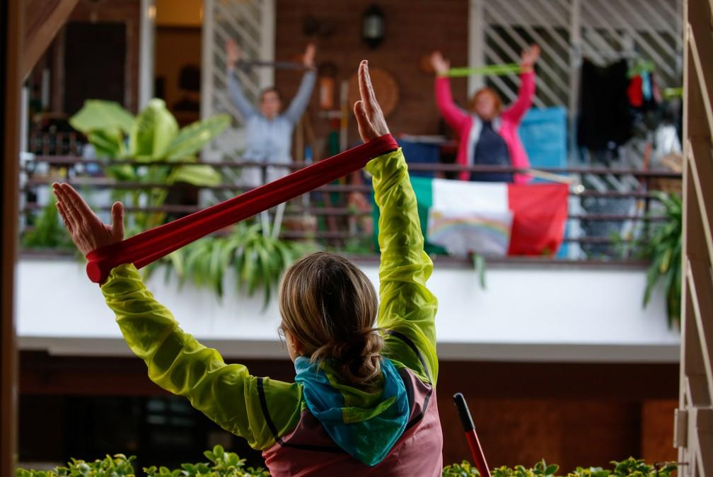A personal trainer Antonietta Orsini realiza uma aula de ginástica para seus vizinhos de sua varanda em Roma, na Itália, durante isolamento para evitar a propagação do coronavírus (COVID-19) em 18 de março — Foto:  Remo Casilli/Reuters