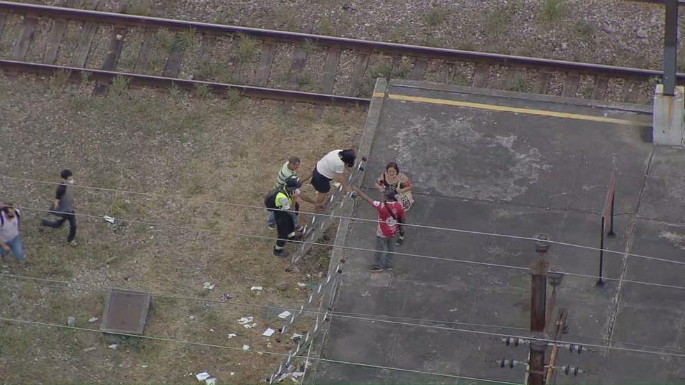 Mulher encontra dificuldade para subir em escada após caminhada nos trilhos dos trens da Supervia — Foto: Reprodução/ TV Globo