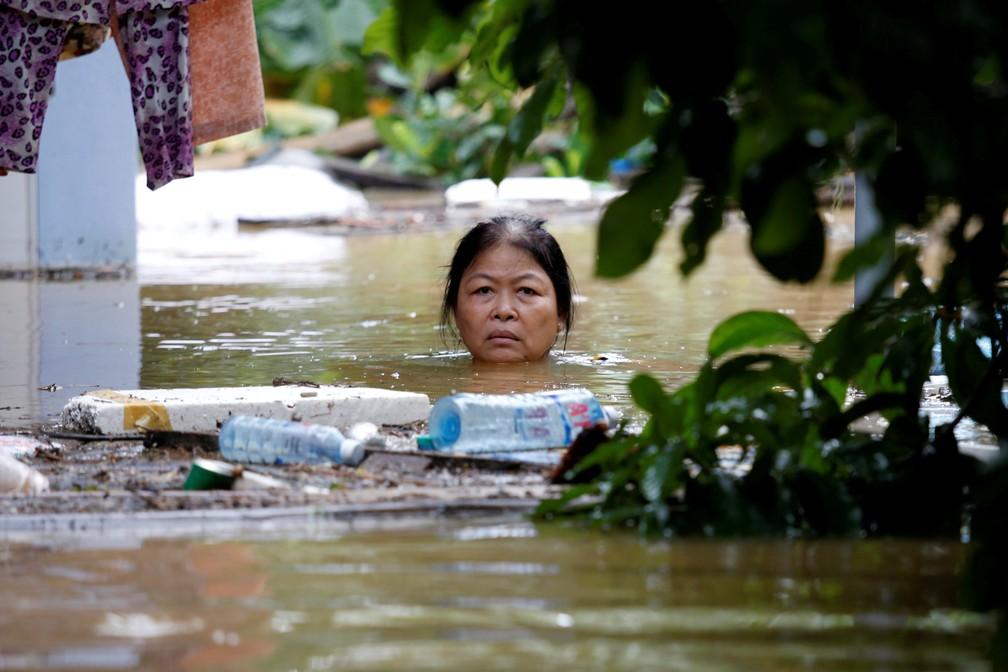 Mulher na cidade de Hoi An atravessa rua com água na altura do pescoço; cidade sofreu enchente após passagem do tufão Damrey (Foto: Kham/Reuters)