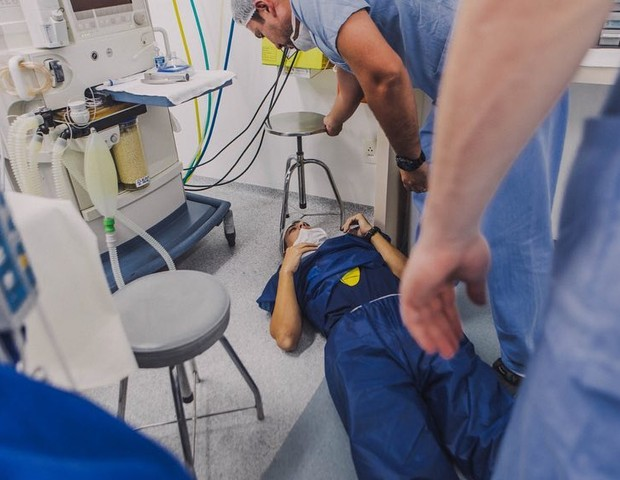 Pai deitado no chão da sala de parto (Foto: Bruna Costa)